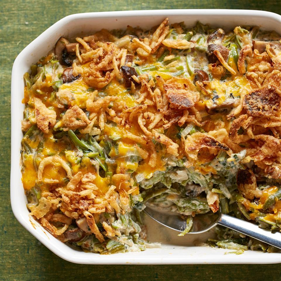 white casserole dish with green bean casserole with a serving spoon in the dish