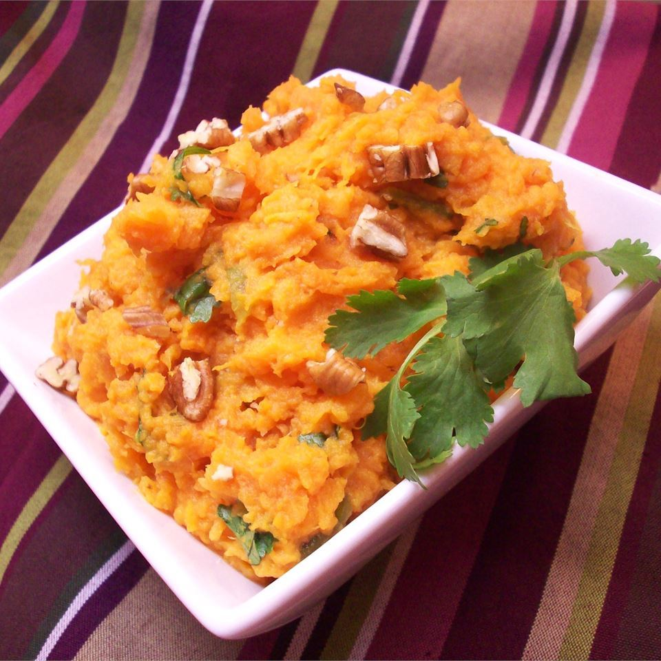 Mashed Jalapeno-Cilantro Sweet Potatoes in a white dish with herb garnish