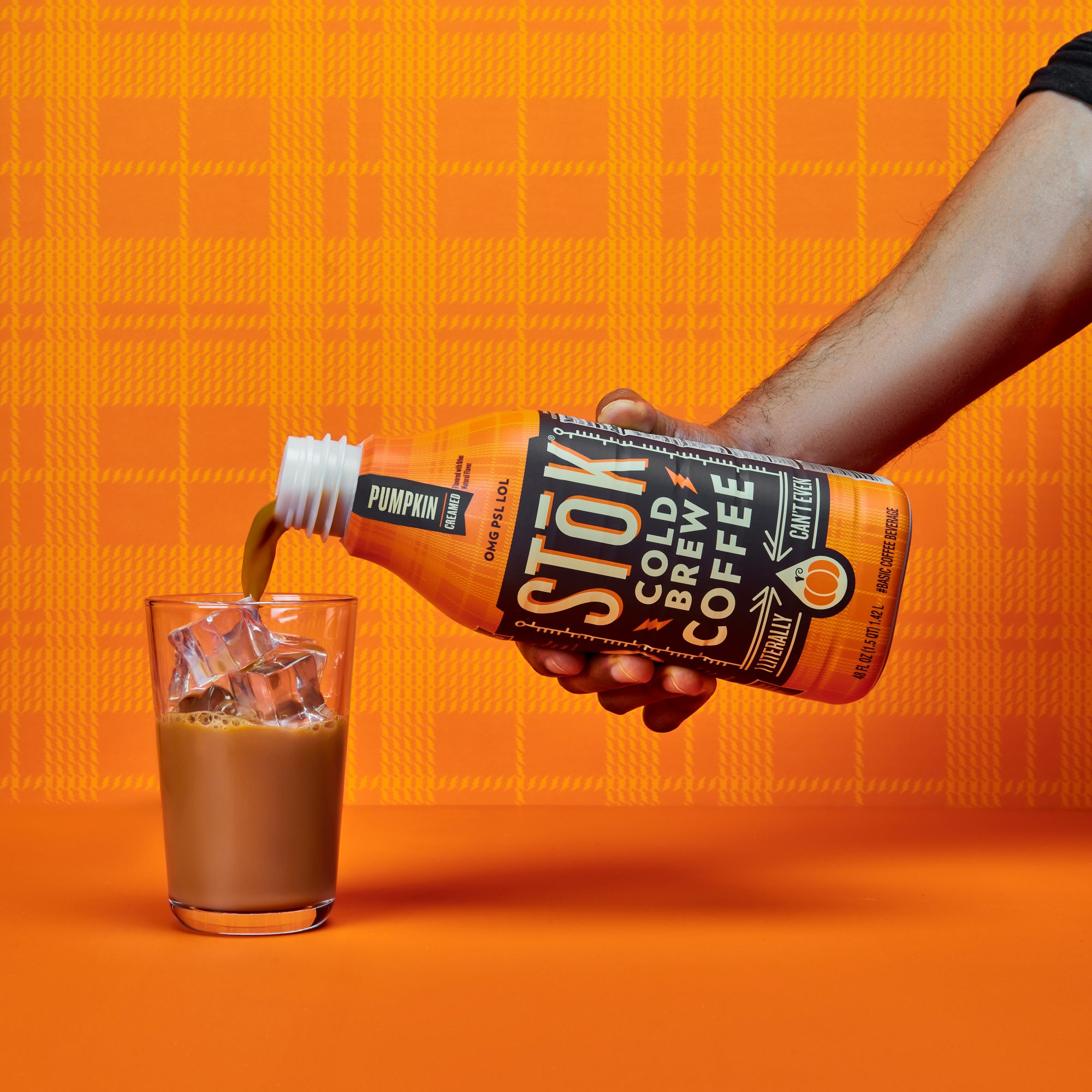 STok Pumpkin Lifestyle Bottle being poured into a tall glass with ice