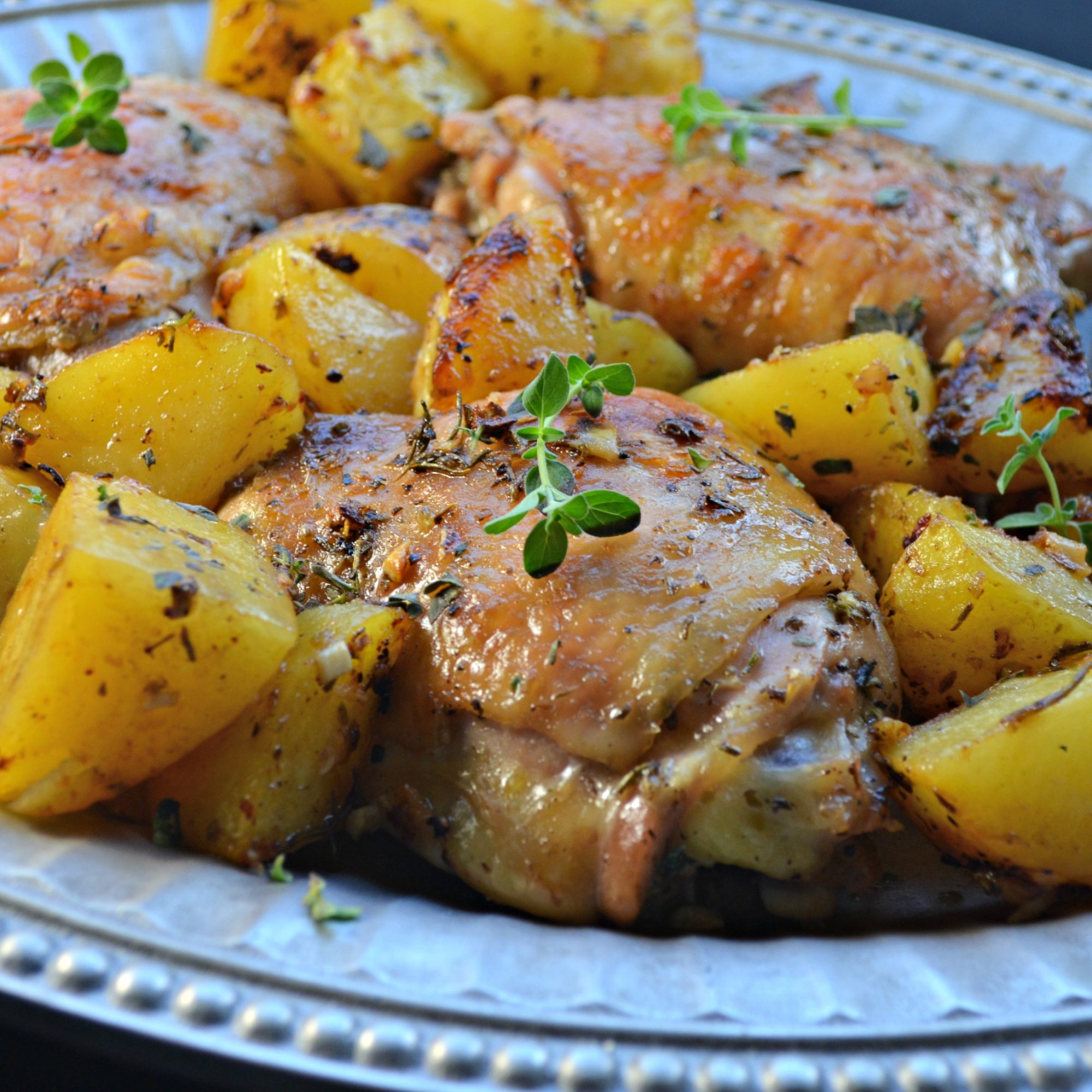 A platter of chicken thighs and roasted potatoes, garnished with fresh thyme
