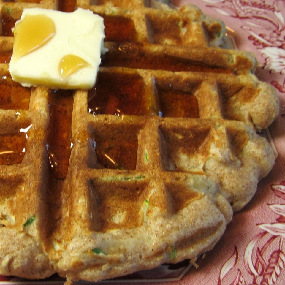 Zucchini Oatmeal Waffles with butter and syrup on a red plate