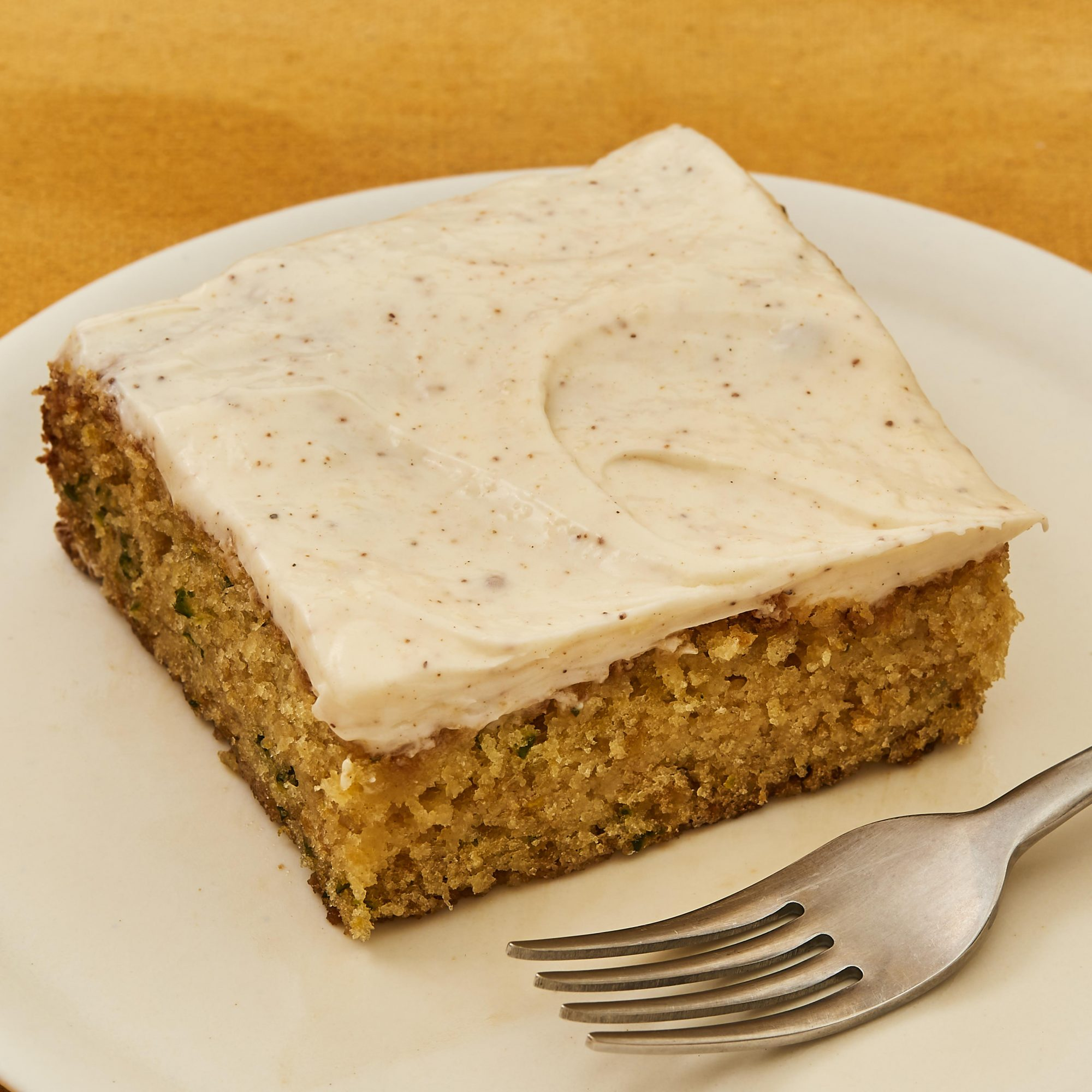 Slice of zucchini cake frosted with cream cheese applesauce icing