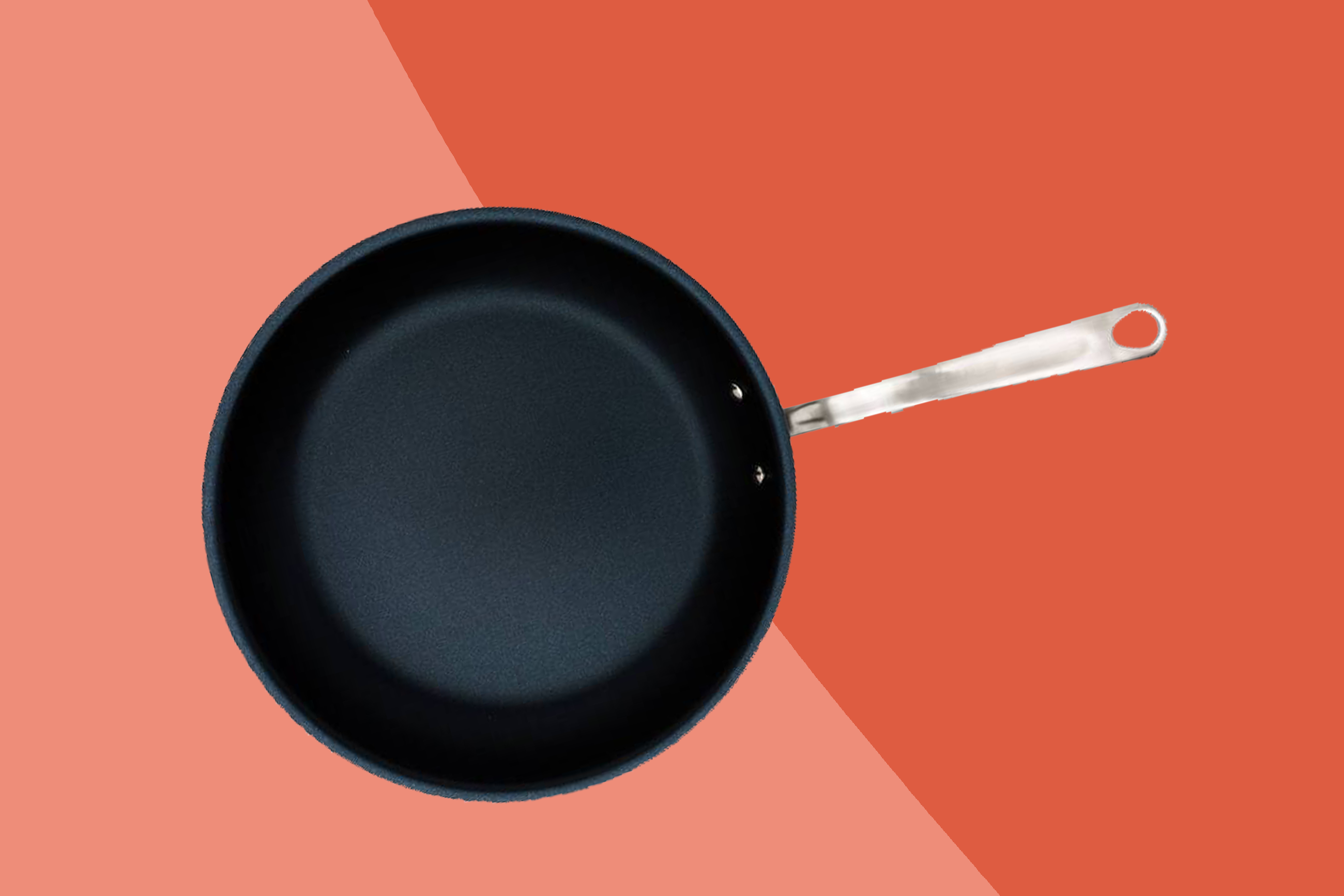 A made-in nonstick skillet on a two-tone orange and pink background