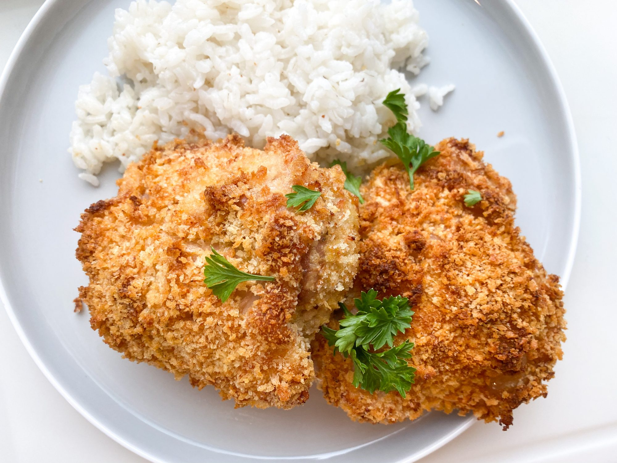 oven fried chicken thighs with crispy coating on a plate with white rice