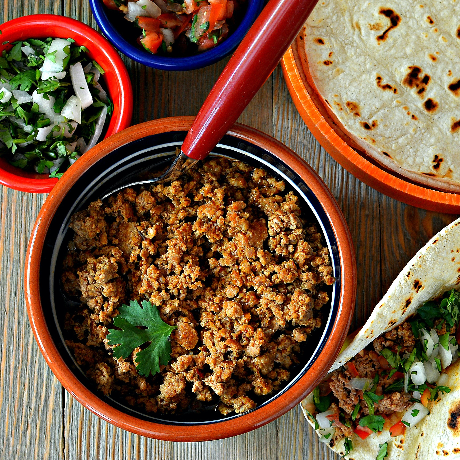 ground turkey in a red bowl with tortillas and garnishes
