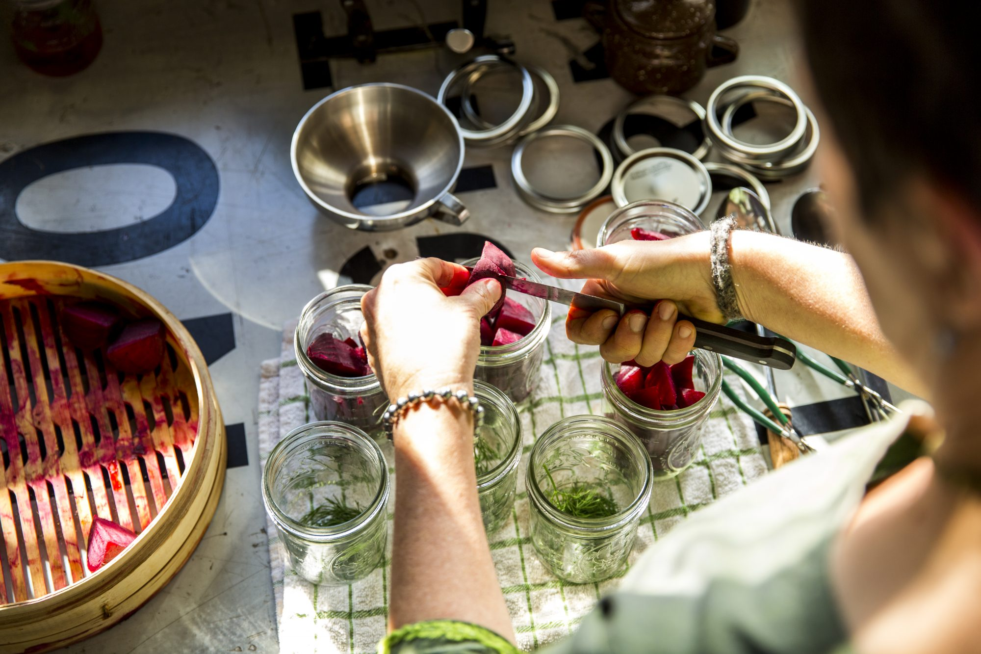 Over the shoulder view of woman slicing beetroot into preserves jar in kitchen