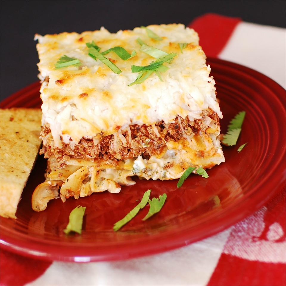 Ground Turkey Noodle Bake on a red plate with garlic bread