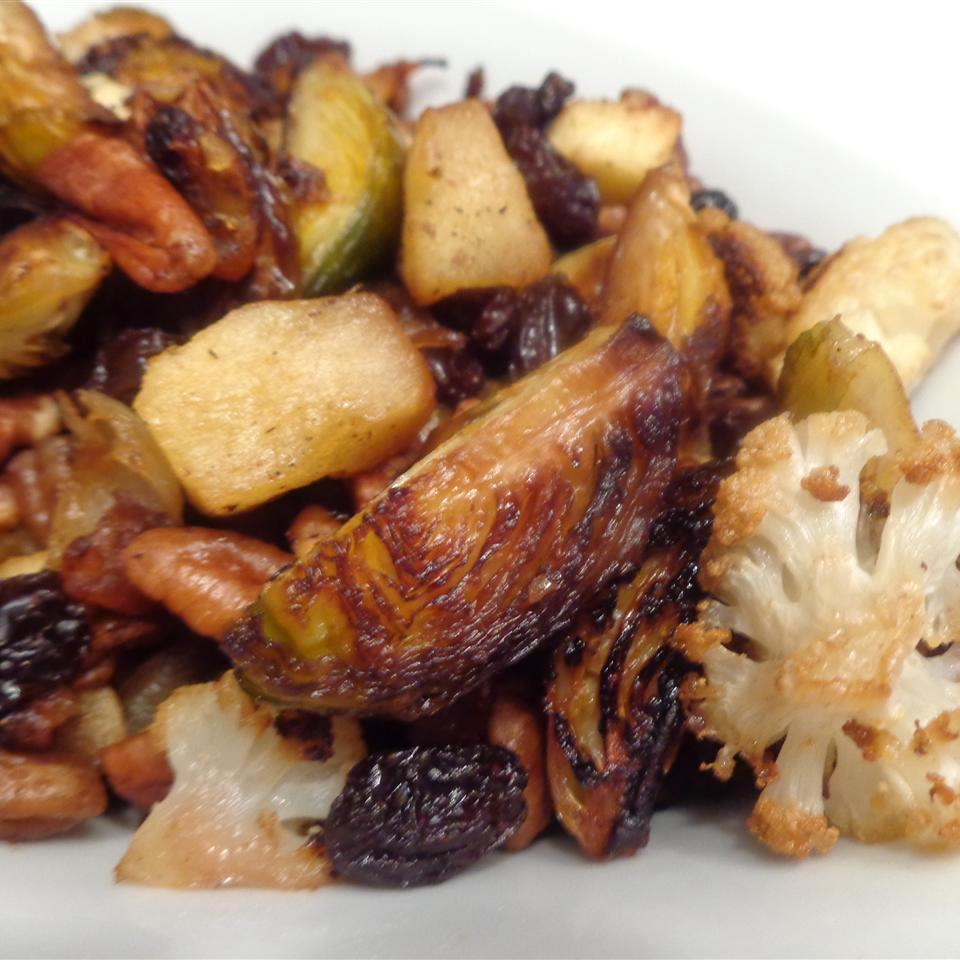 Roasted Brussels Sprouts with Apples, Golden Raisins, and Walnuts on a white dish