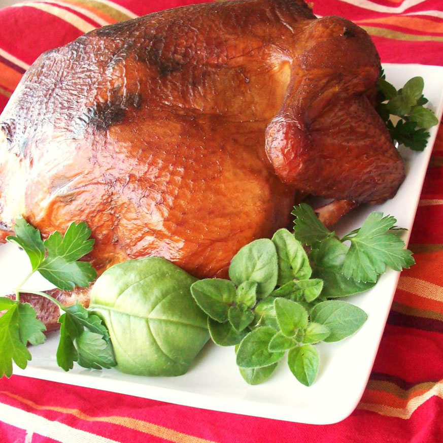 Whole smoked chicken on white platter with green garnishes