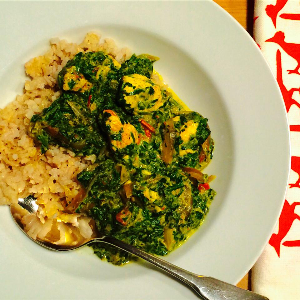 a bowl of Authentic Saag Paneer with a spoon resting in it