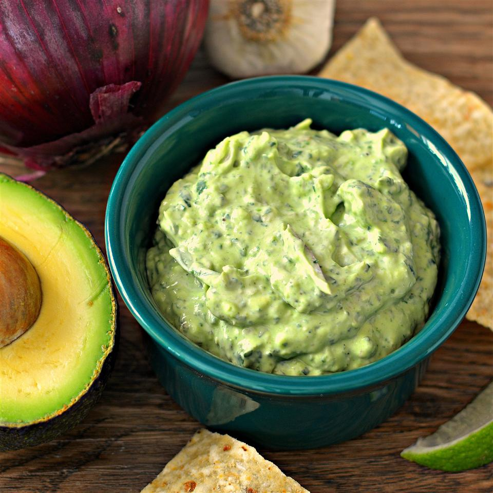a dark green bowl contains Avocado-Spinach Dip; it's surrounded by an avocado, tortilla chips, an onion, and garlic.