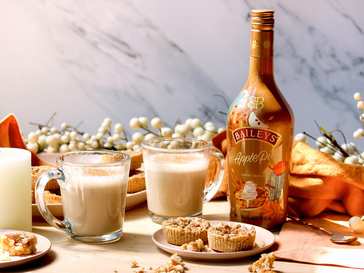 a bottle of baileys apple pie liqueur with two glasses and a plate of cookies