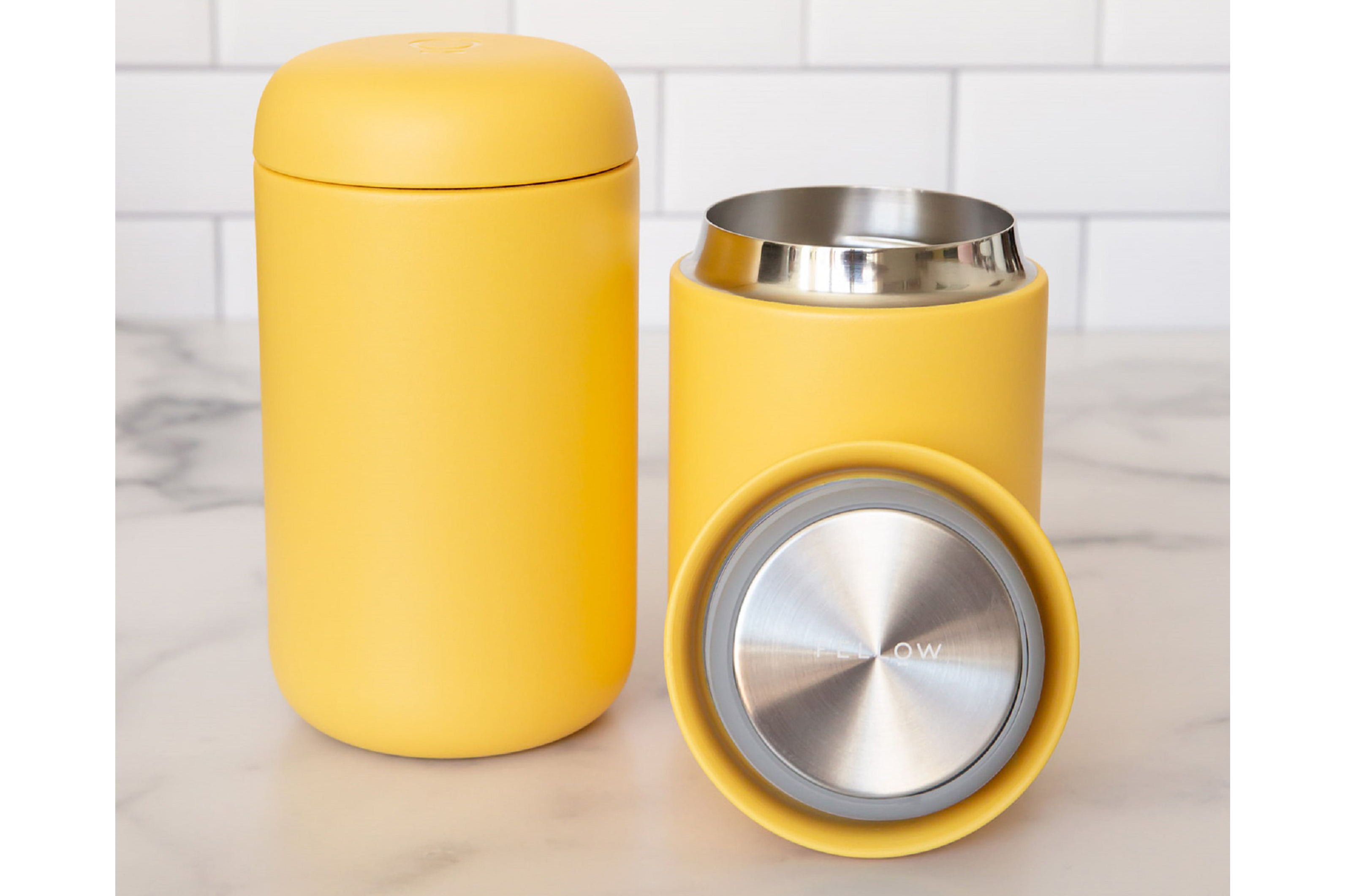 yellow Fellow Carter Everywhere Thermal Mug on a marble counter in front of a white subway tile backsplash