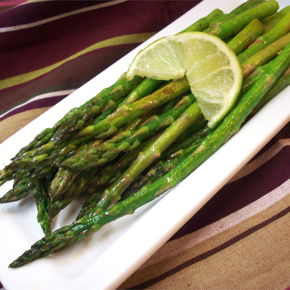 Garlic Asparagus with Lime slice on white platter