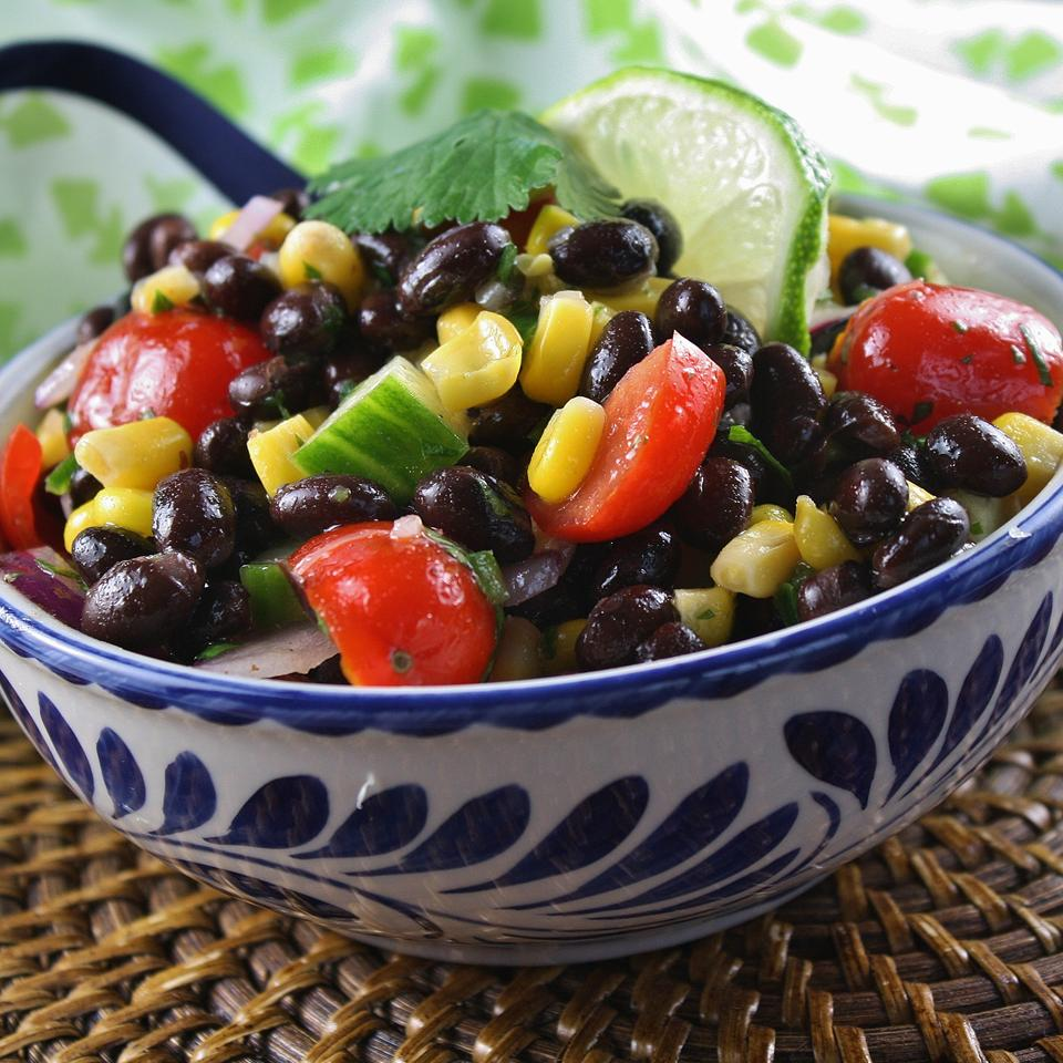 Salad with lime, black beans, corn, and grape tomatoes in blue and white bowl