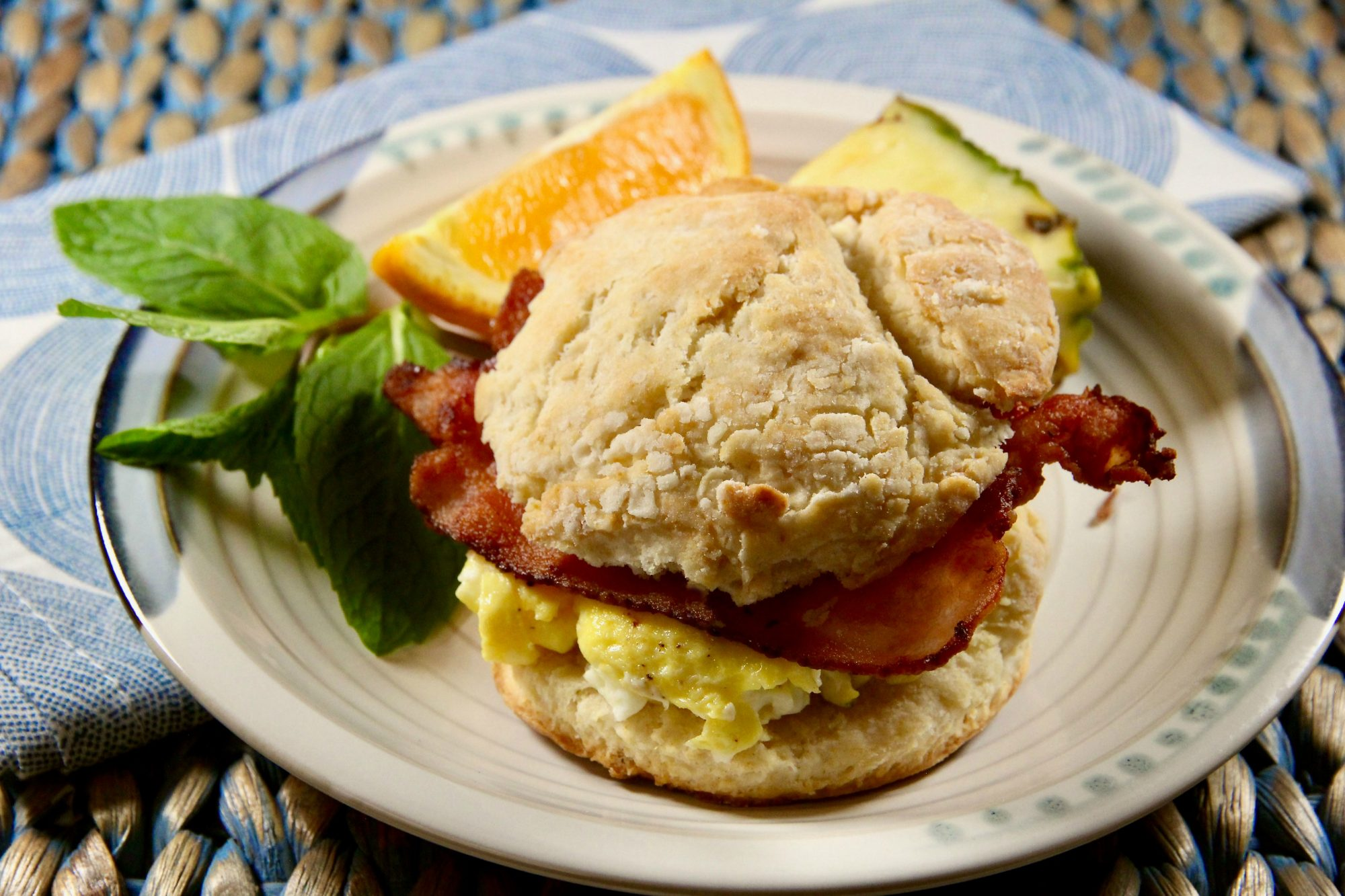 a Bacon, Egg, and Cheese Buttermilk Biscuit Breakfast Sandwich on a white plate with an orange wedge