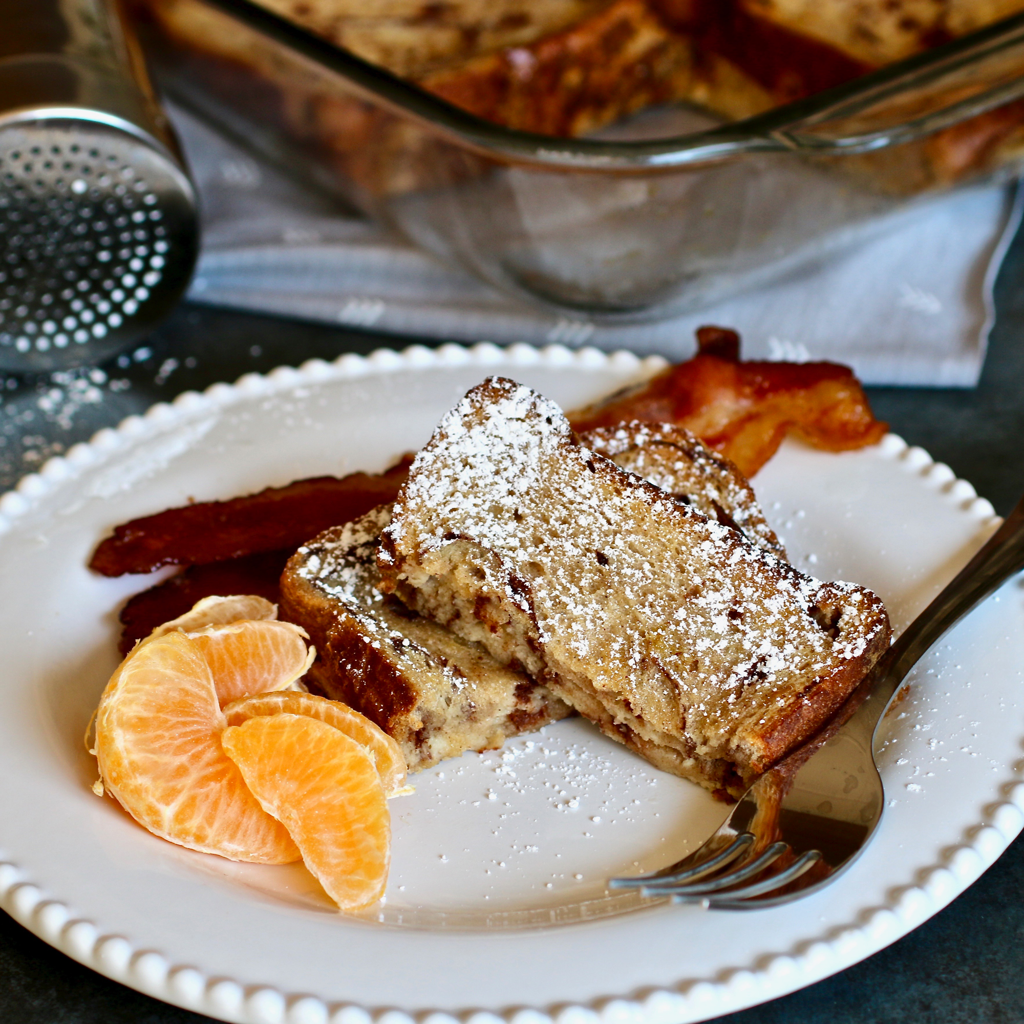 Cinnamon Swirl French Toast Casserole on a plate with a bacon slice and orange slices