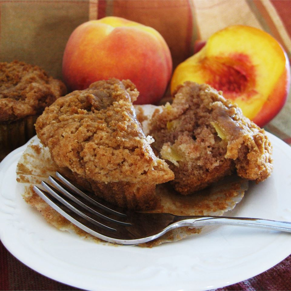 a plate with a Peach Muffin split in half with peaches in the background