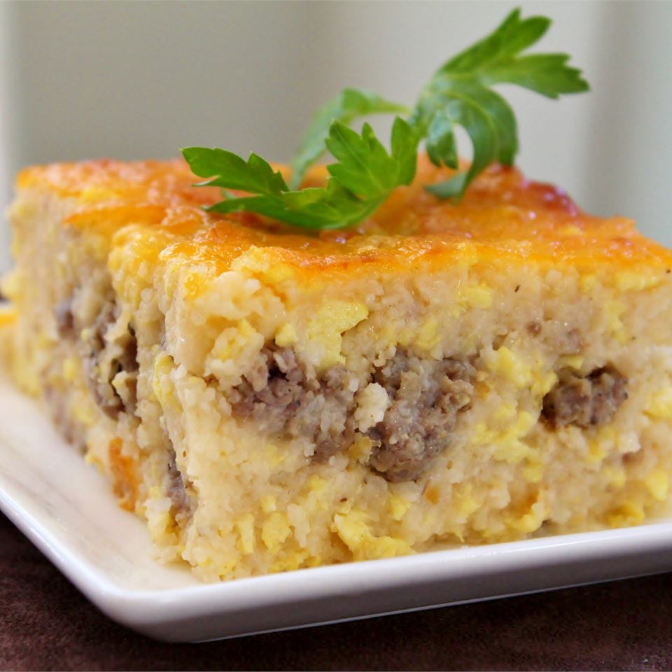 a square slice of Southern Grits Casserole with a sprig of parsley on top