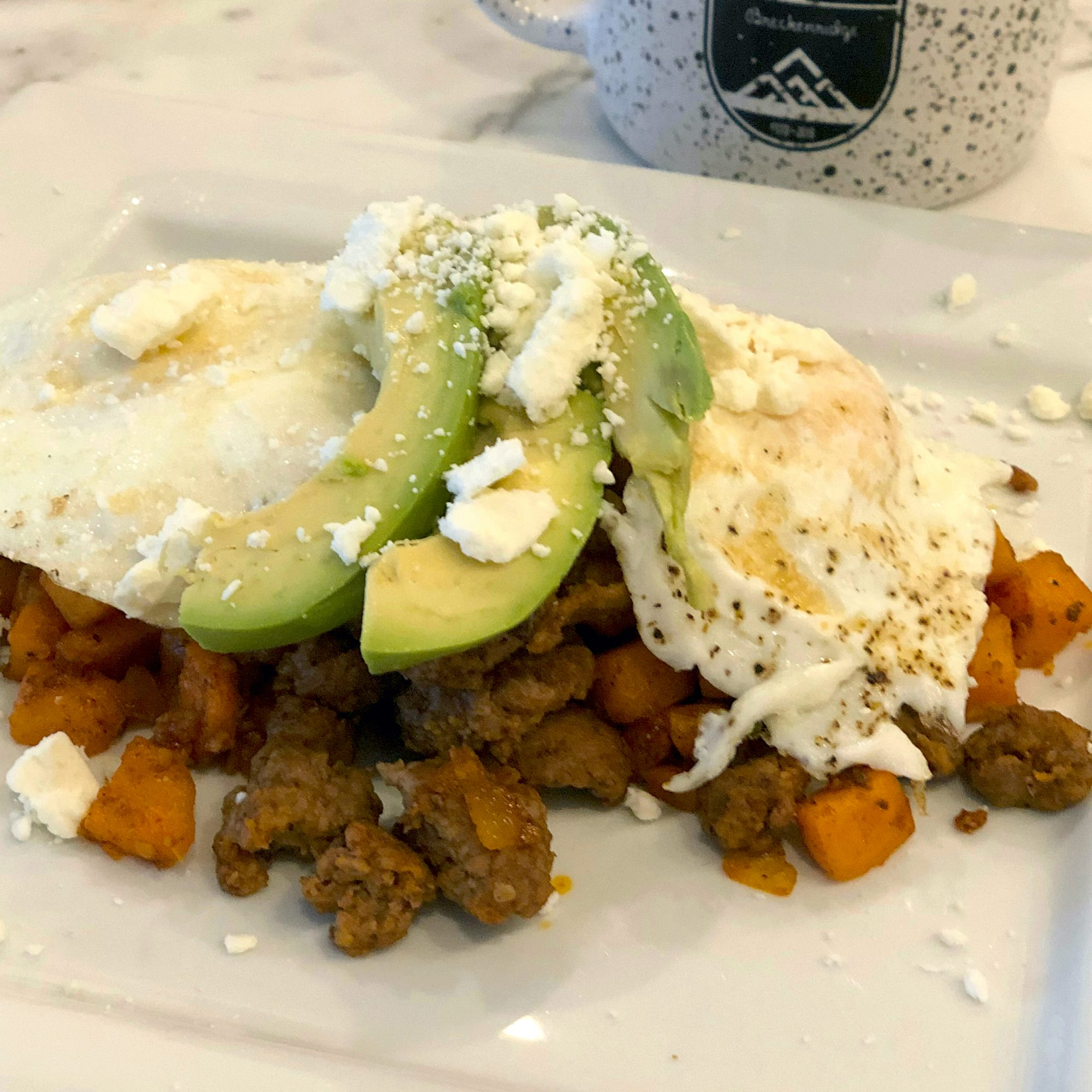 Greek Cowboy Hash and Eggs on a white plate