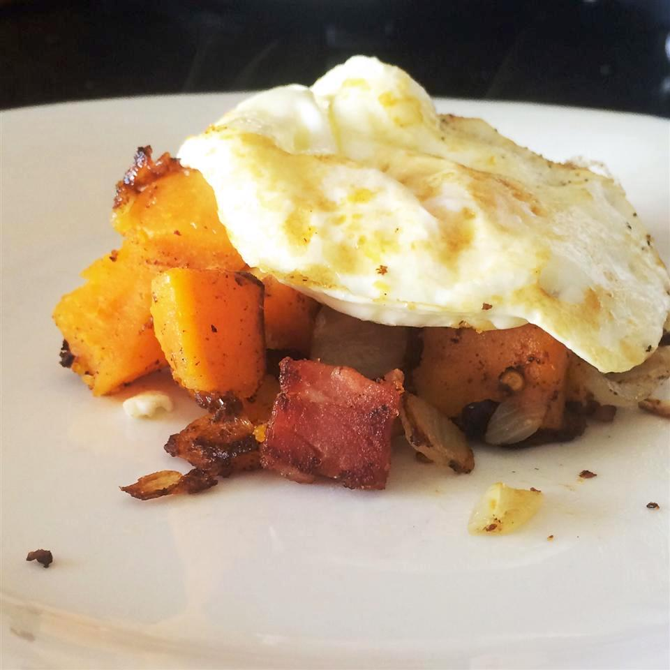 egg over sweet potato cubes on a white plate