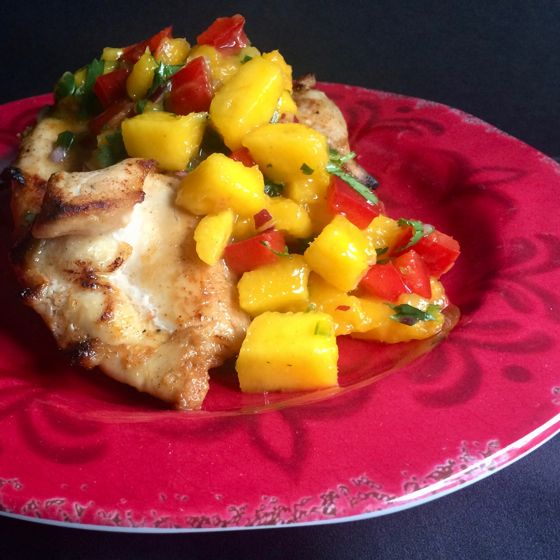 Broiled Chicken Thighs with Mango Salsa on a red plage