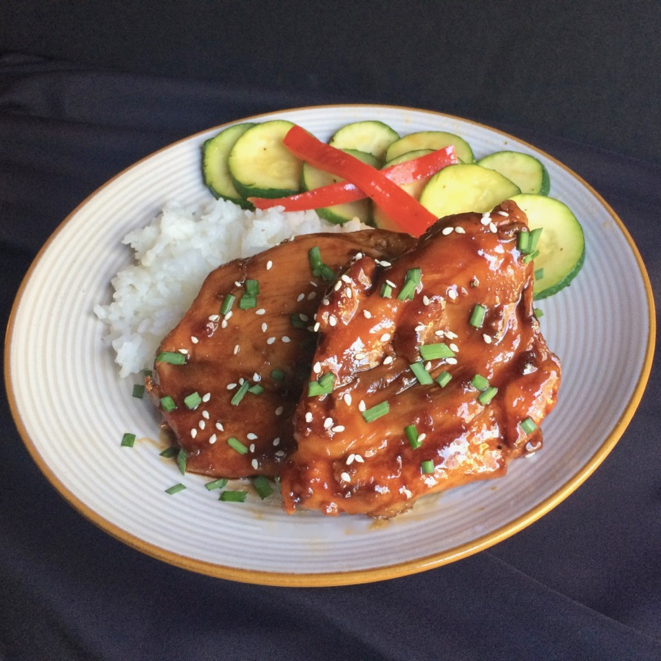 Broiled Teriyaki Chicken Thighs with rice and cucumber salad on a white plate