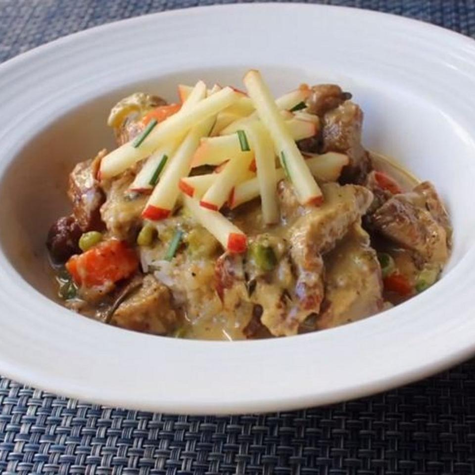 a wide-rimmed white bowl holds Creamy Pork Stew with apple slaw on top