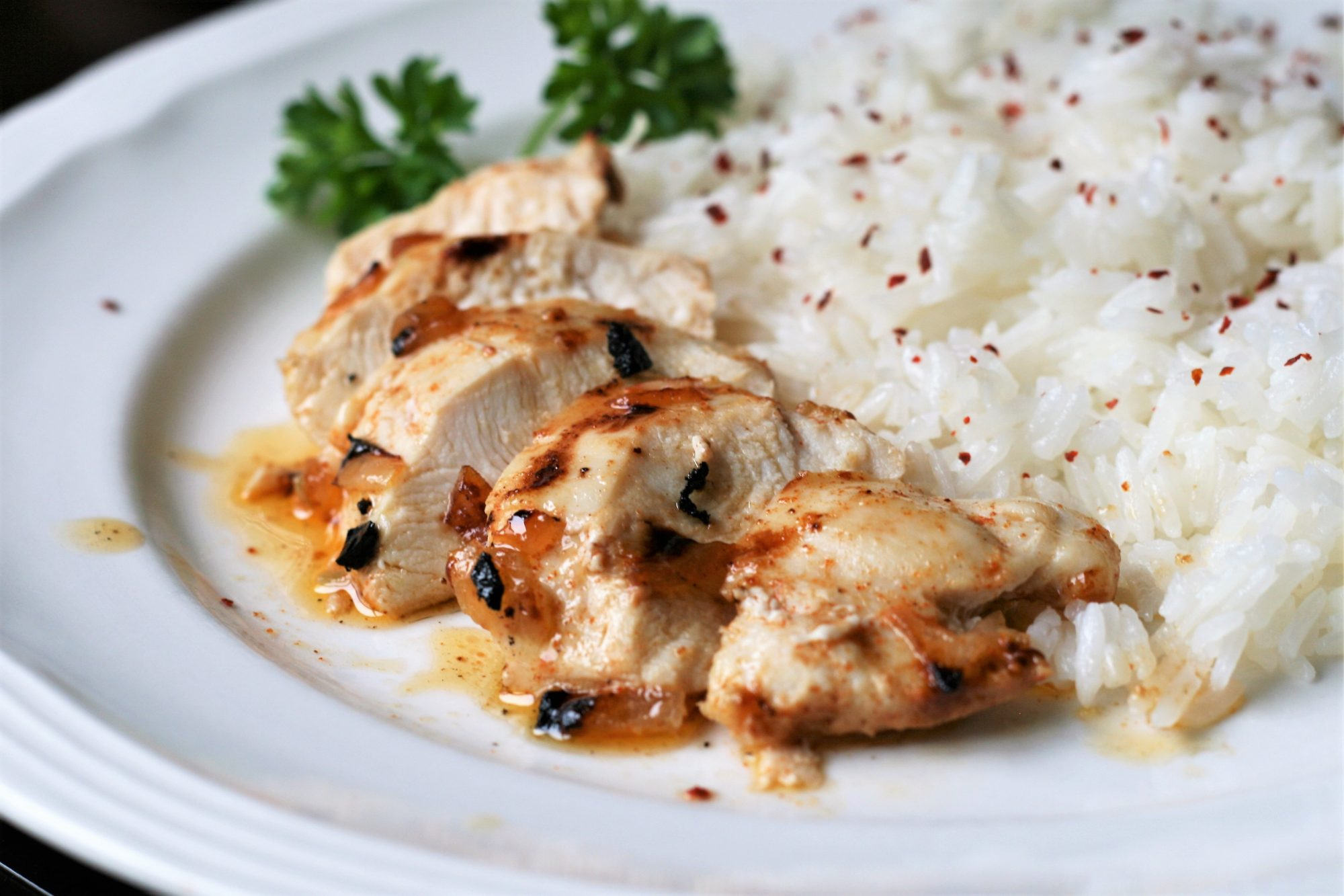 a white plate with Easy Broiled Chicken Breast in slices and white rice with pepper