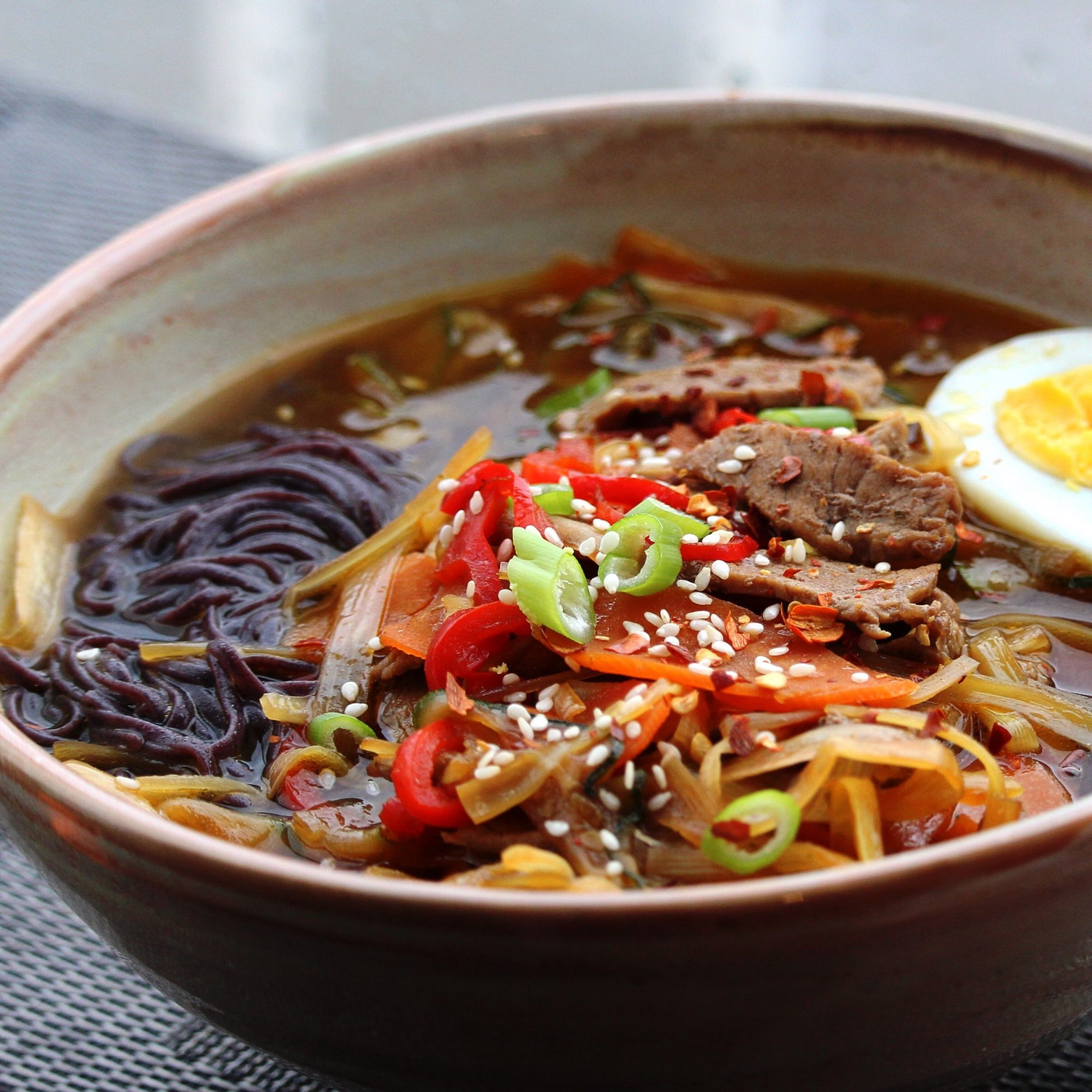 bowl of Asian-Themed Beef and Rice Noodle Soup with an egg on top
