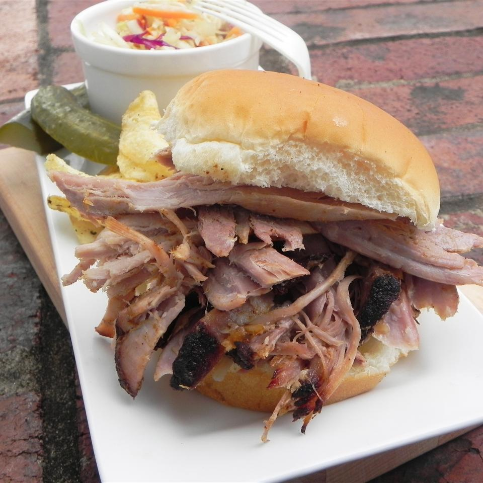 a sandwich made with Maple-Brined and Apple-Smoked Pork Butt, slaw, and a pickle on a long white rectangle plate