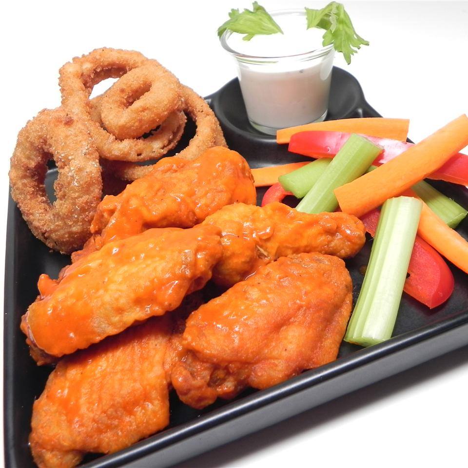 a black plate holds The Perfect Buffalo Wing Sauce, onion rings, and celery with a cup of ranch