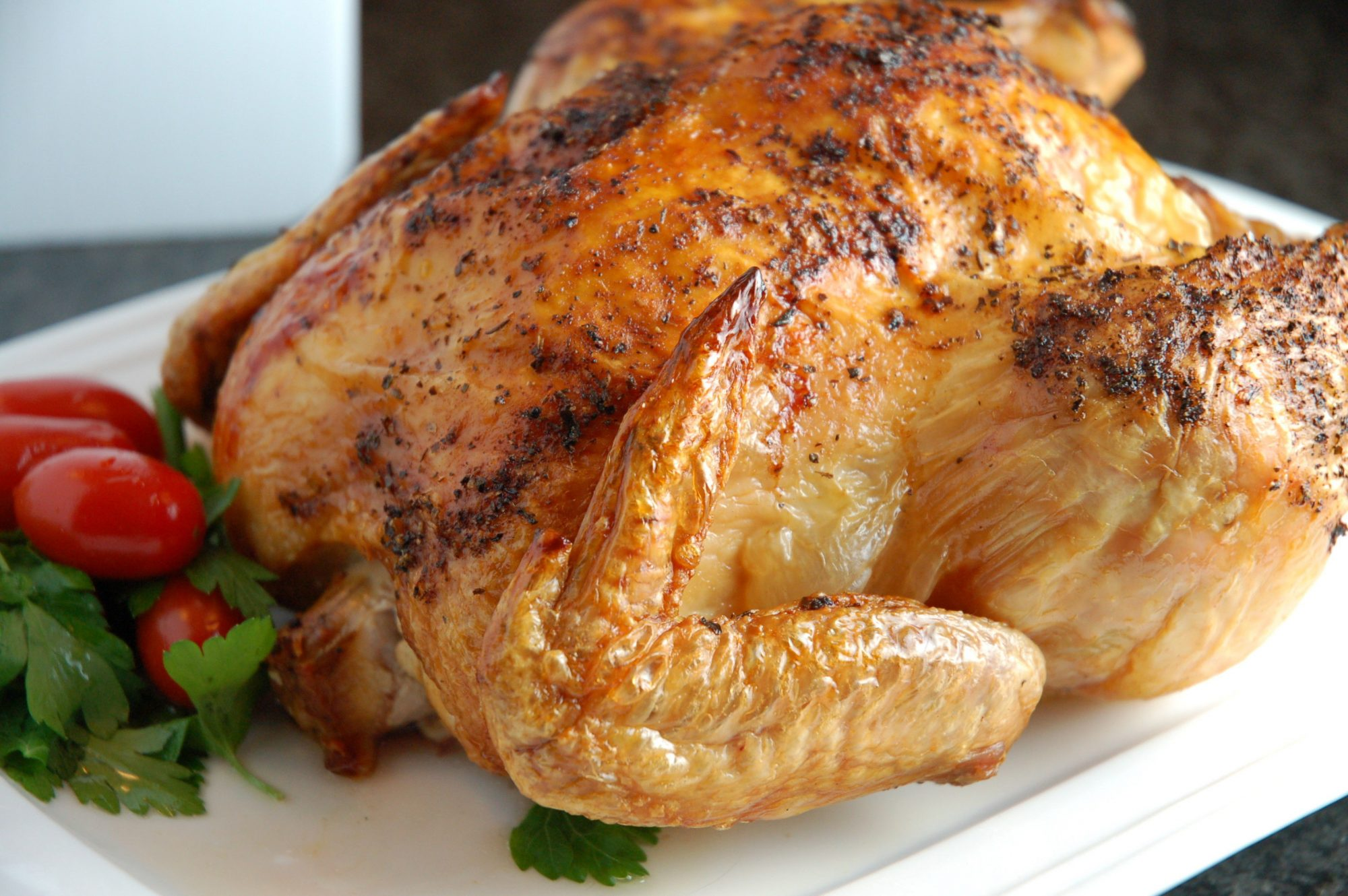 A spice-rubbed roast chicken garnished with parsley and grape tomatoes