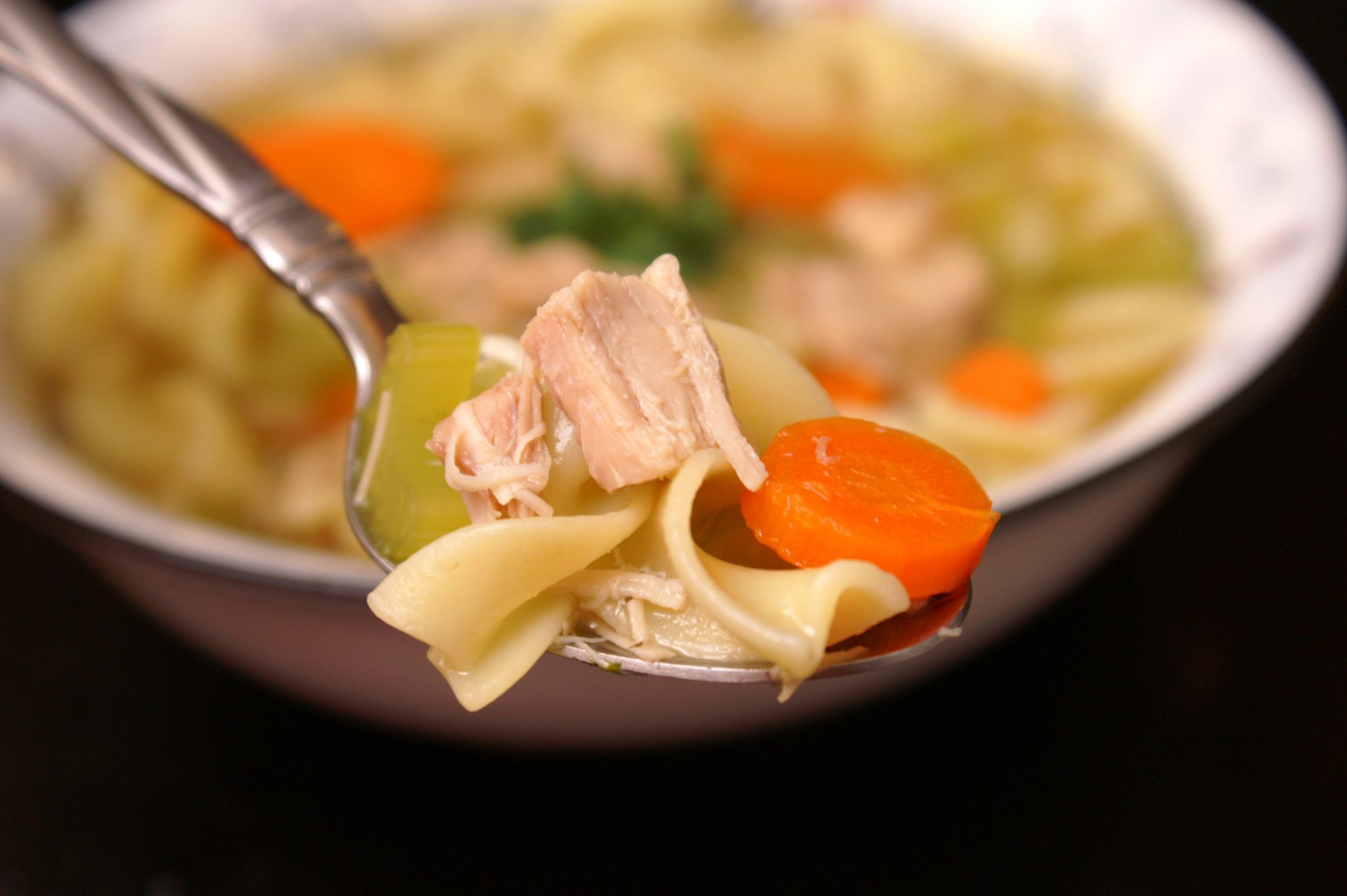 A spoonful of soup with chicken pieces, carrot, and a noodle in the foreground with a bowl of soup behind it
