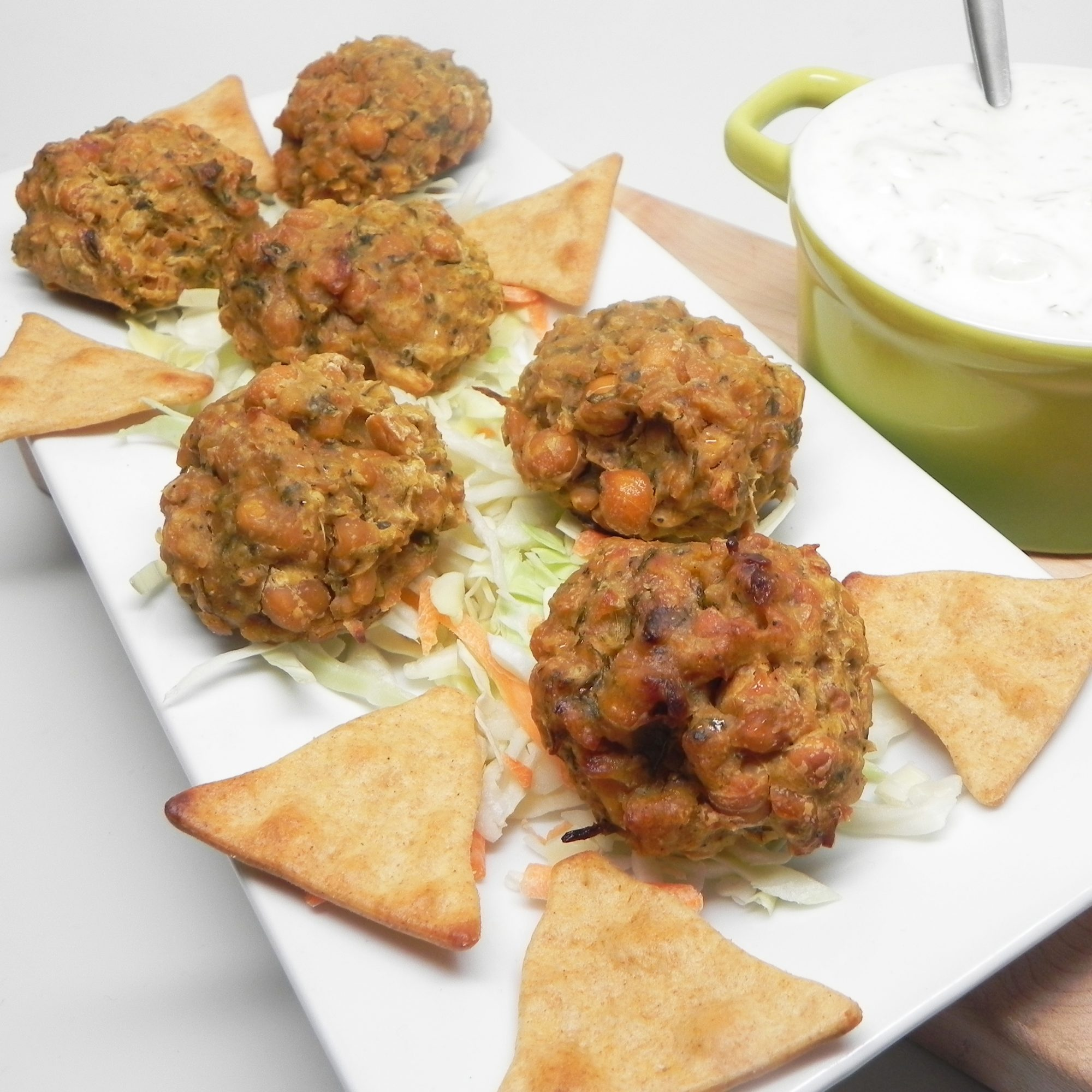 Easy Baked Falafel with Cucumber-Yogurt Sauce and pita bread on a white plate