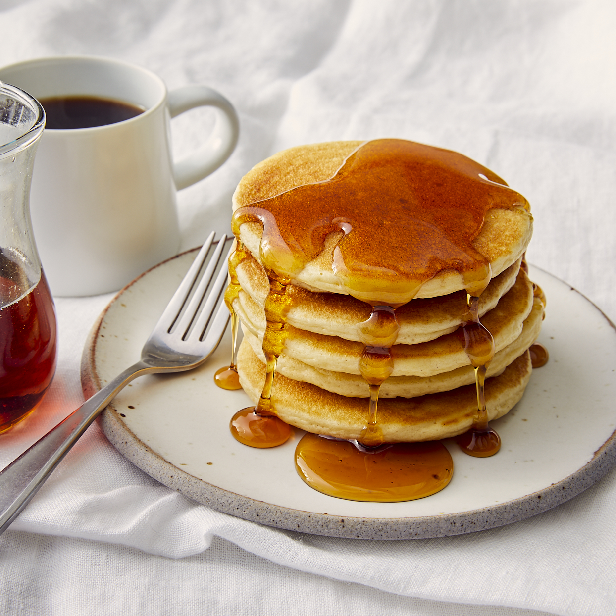 high stack of pancakes covered in syrup