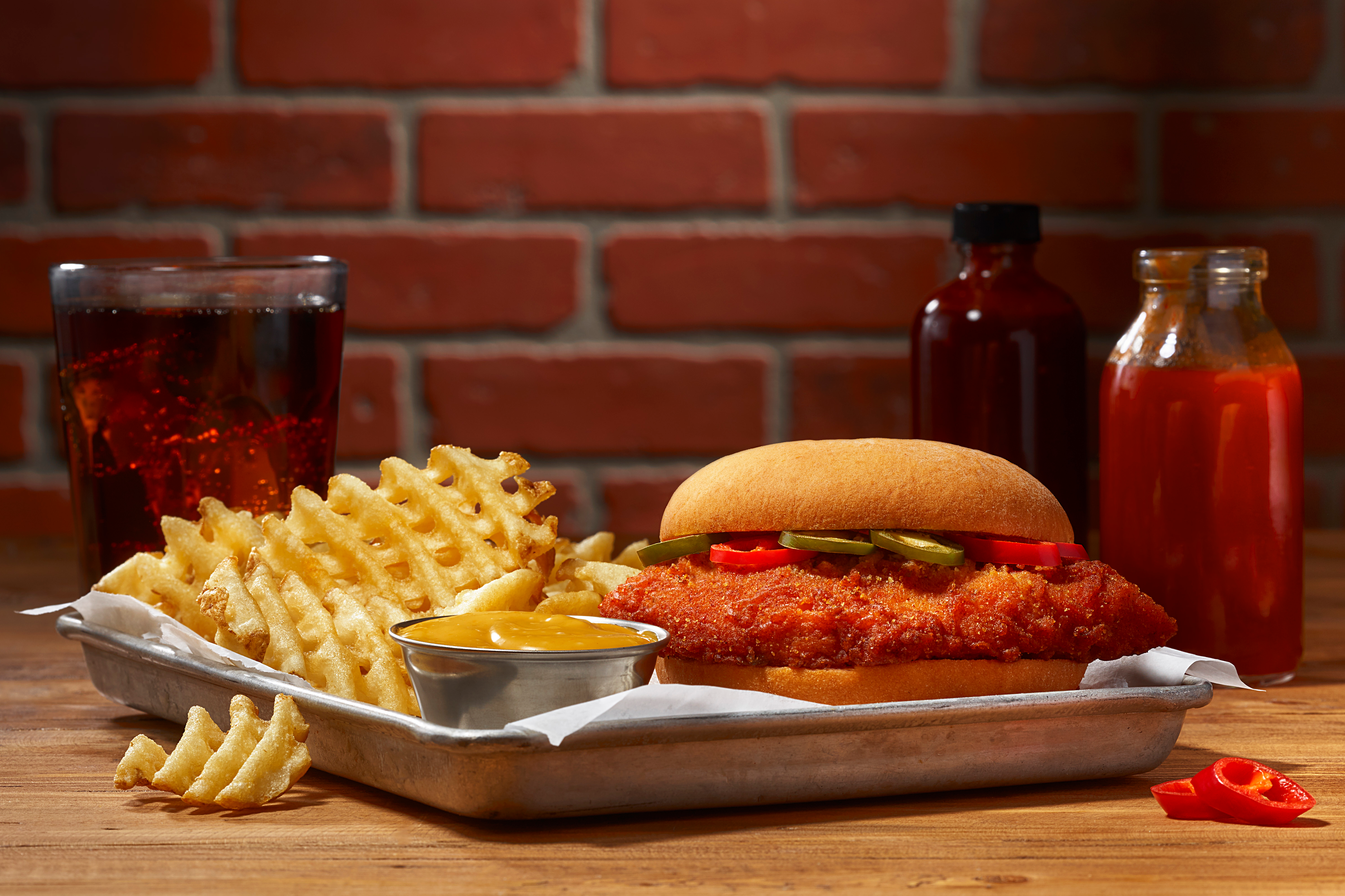 Member's Mark Southern Style Spicy Chicken Sandwich on a tray with waffle fries and a coke in the background