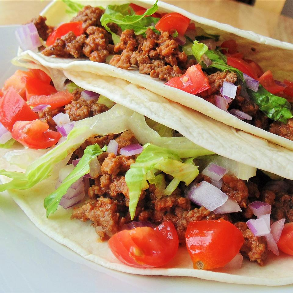 Turkey tacos with lettuce, onions, and tomatoes on white plate