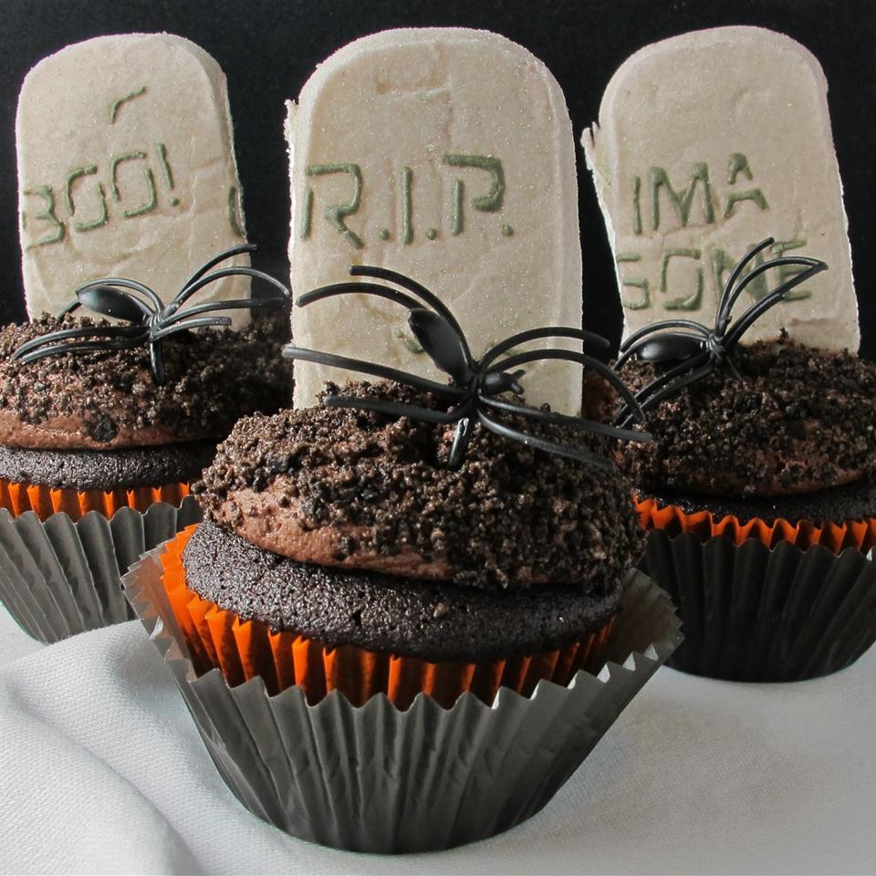 Halloween cupcakes decorated with plastic spiders and cookie tombstones