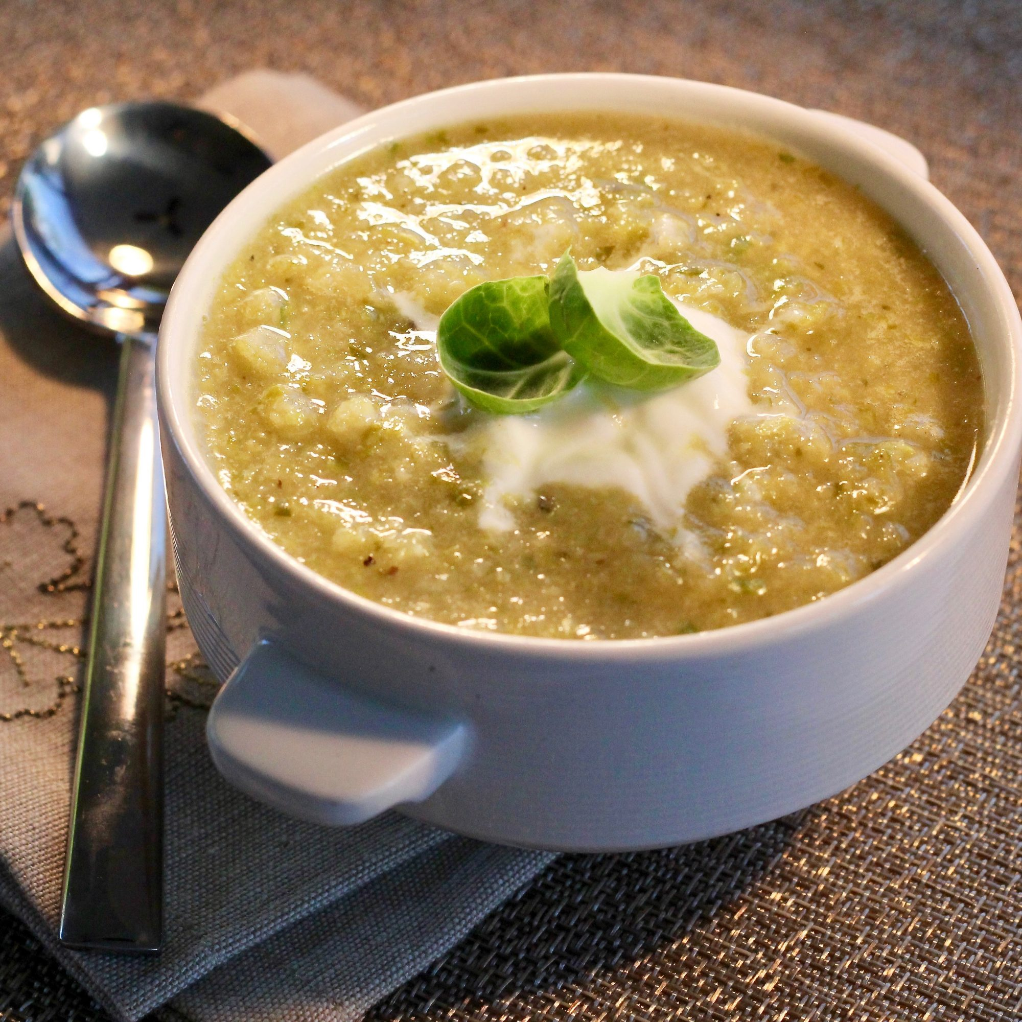 Brussels Sprouts Soup in a white bowl with sour cream topping