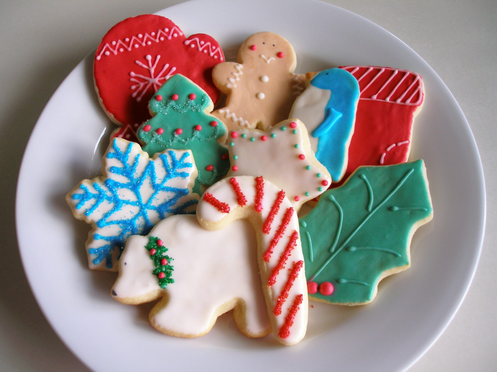 A plate of assorted frosted cookies: candy cane, polar bear with a wreath around its neck, snowflake, mitten, holly leaf, Christmas tree