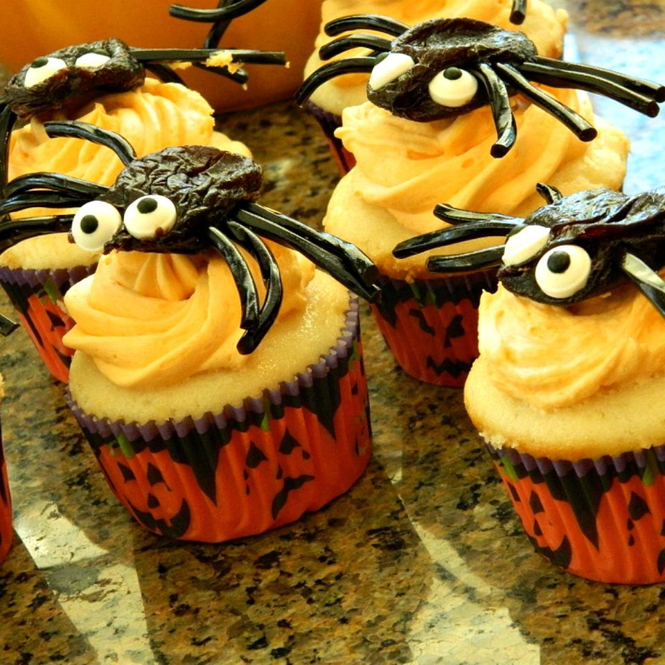 Halloween cupcakes topped with a swirl of orange-tinted frosting and spiders with prune bodies and black licorice legs