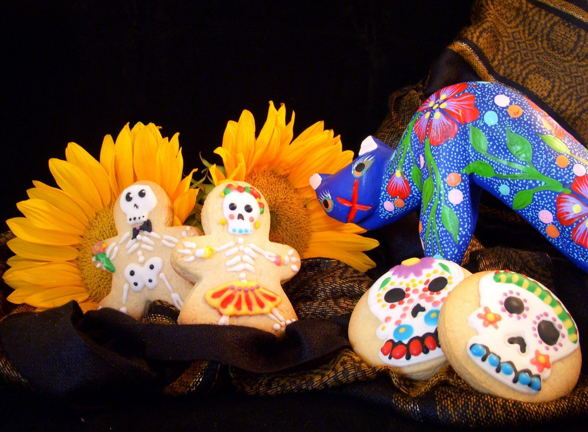 Day of the Dead cookies decorated to look like colorful skulls and skeletons