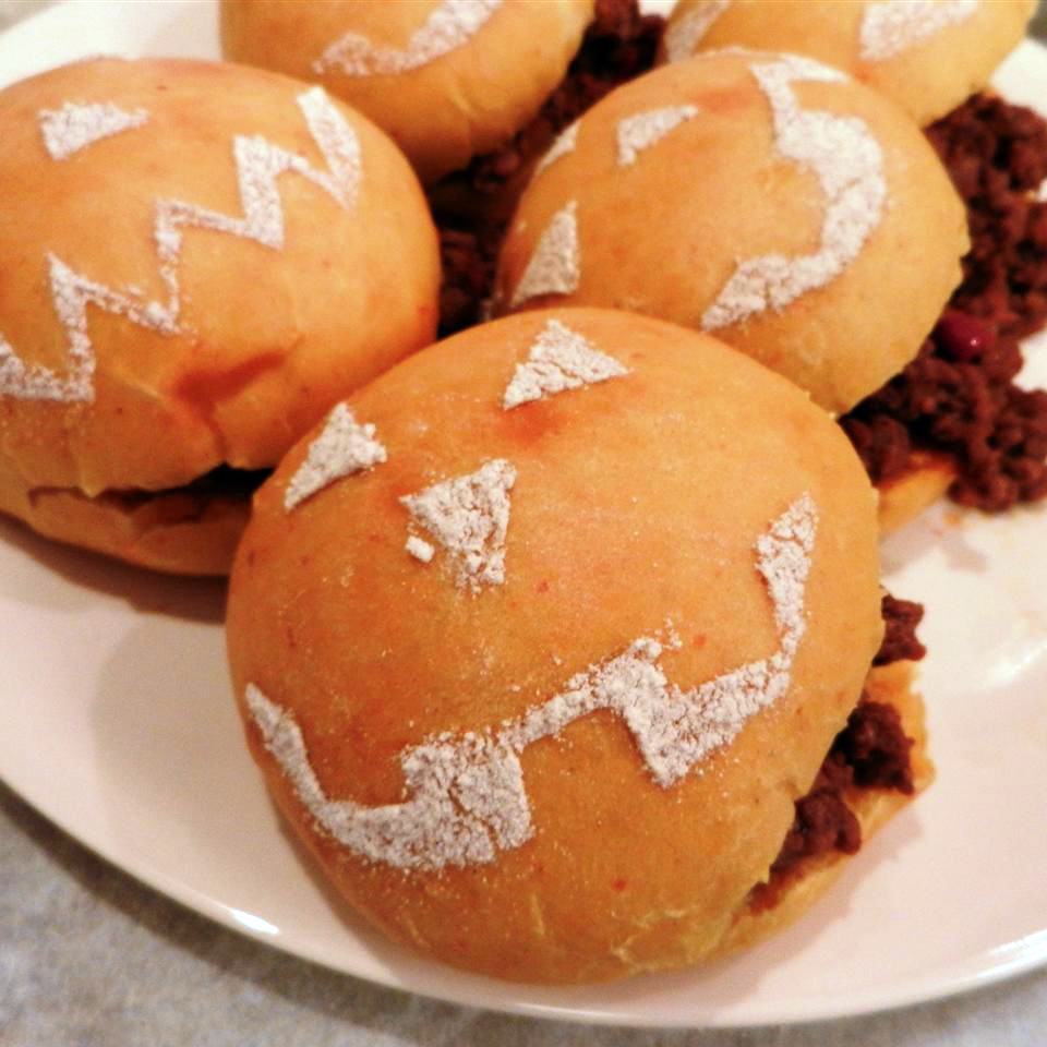 A plate of sloppy joes on buns decorated to look like jack o' lanterns