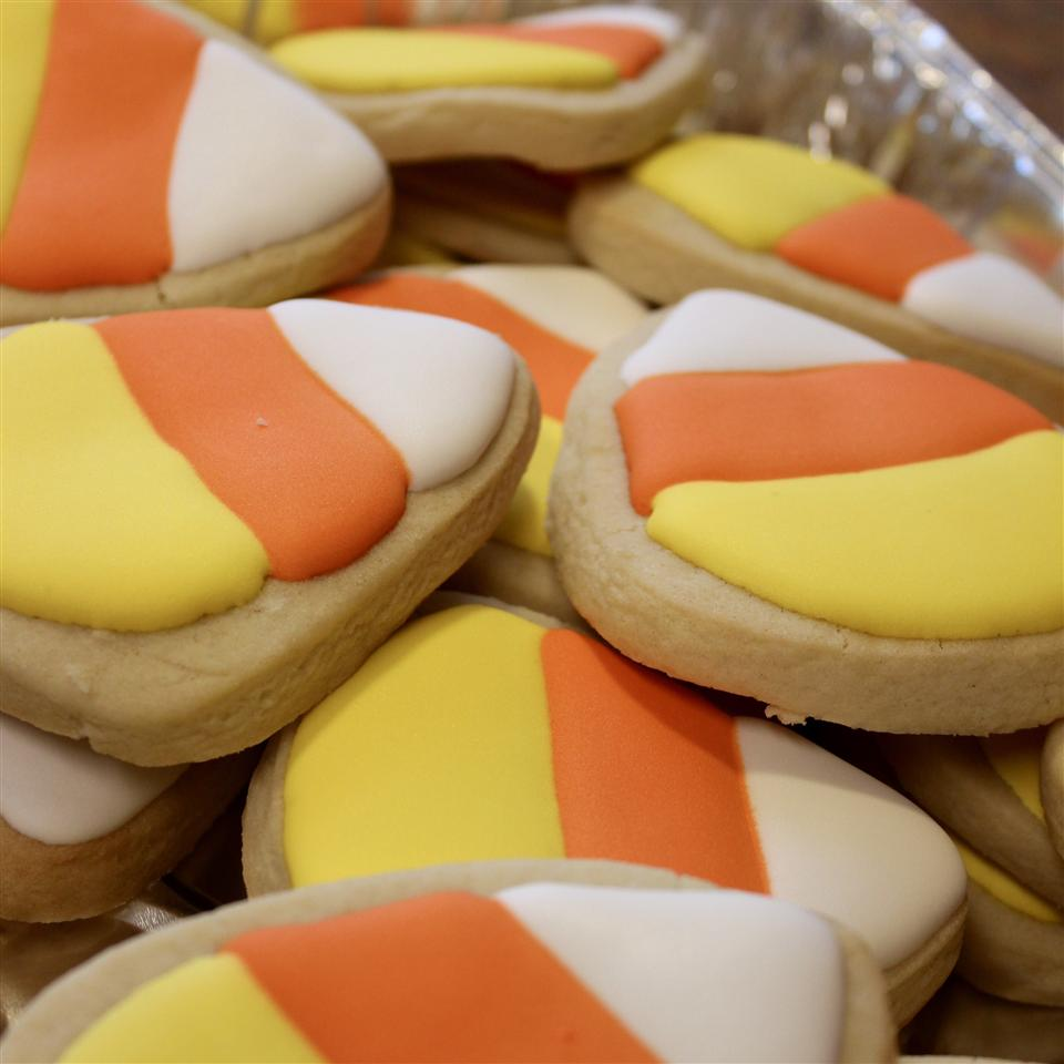 Triangular sugar cookies decorated with white, orange, and yellow icing to look like candy corn