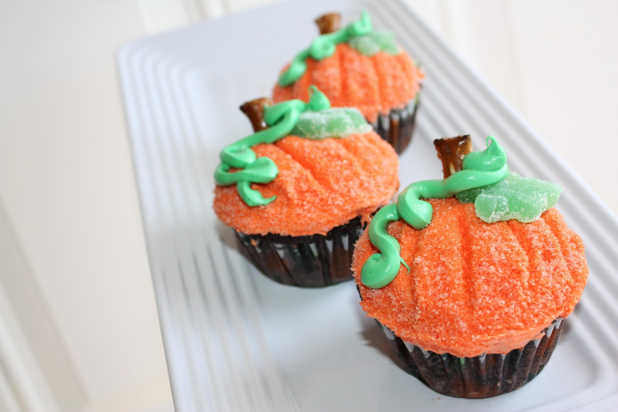Cupcakes decorated to look like pumpkins with orange frosting, pretzel rod stems, and piped green vines