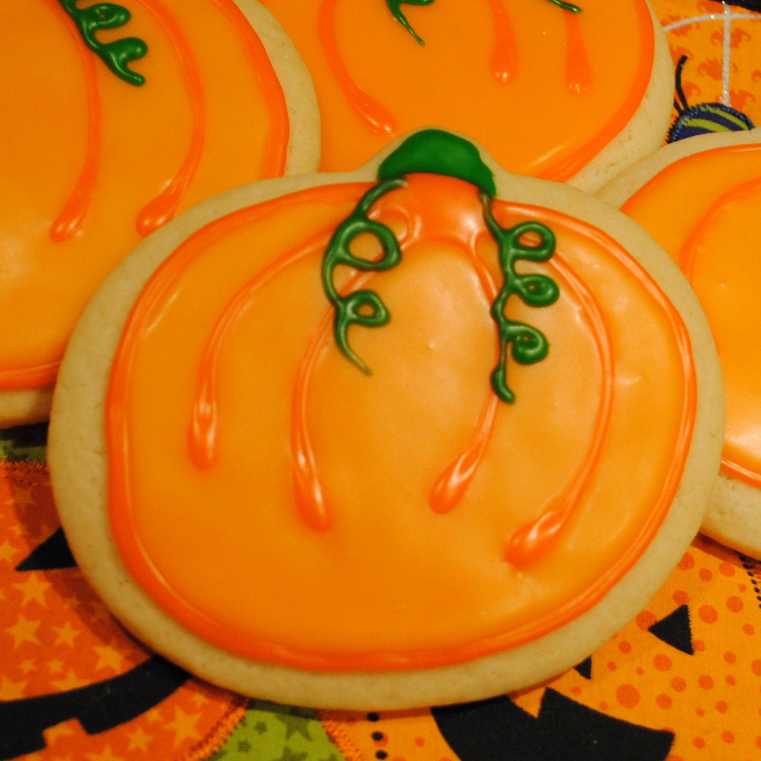 Pumpkin-shaped cookies decorated with orange icing with green stems and vine tendrils