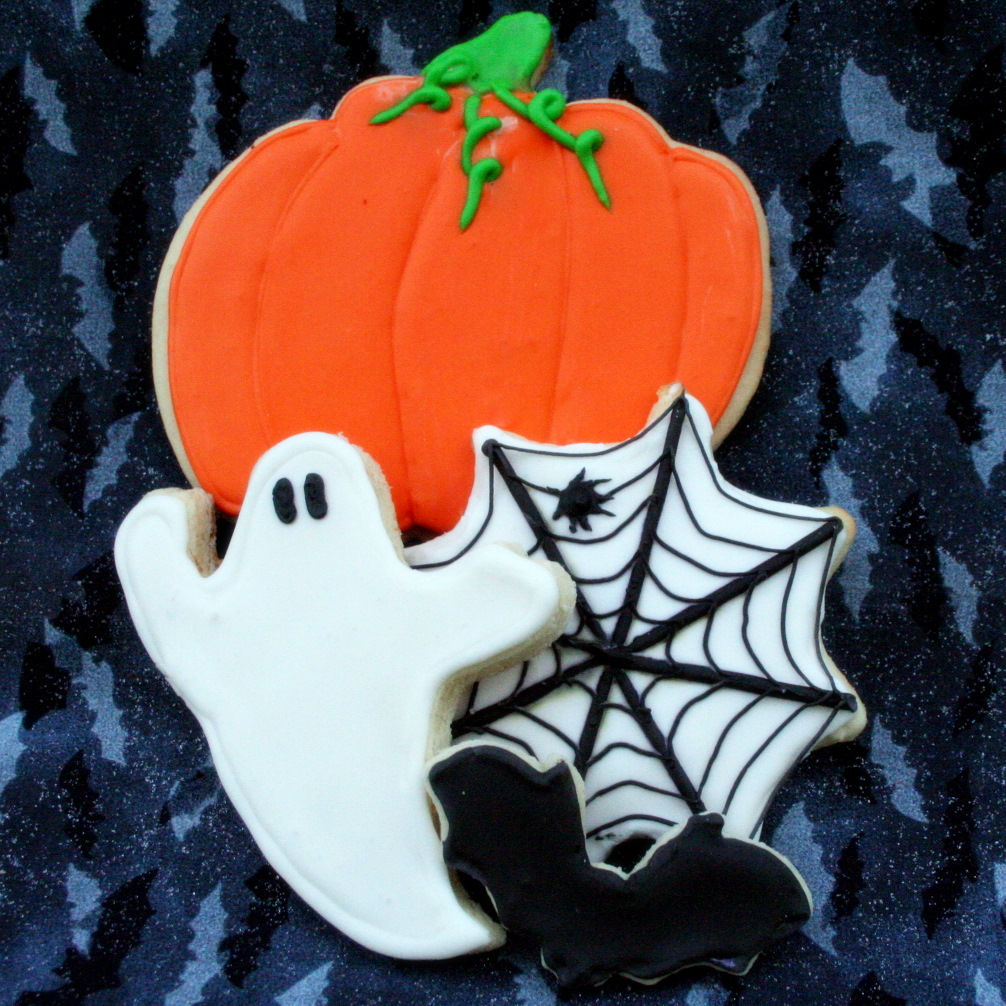 a trio of Halloween cookies: a ghost, a black spiderweb on a white background, and an orange pumpkin with a green stem and vine tendrils