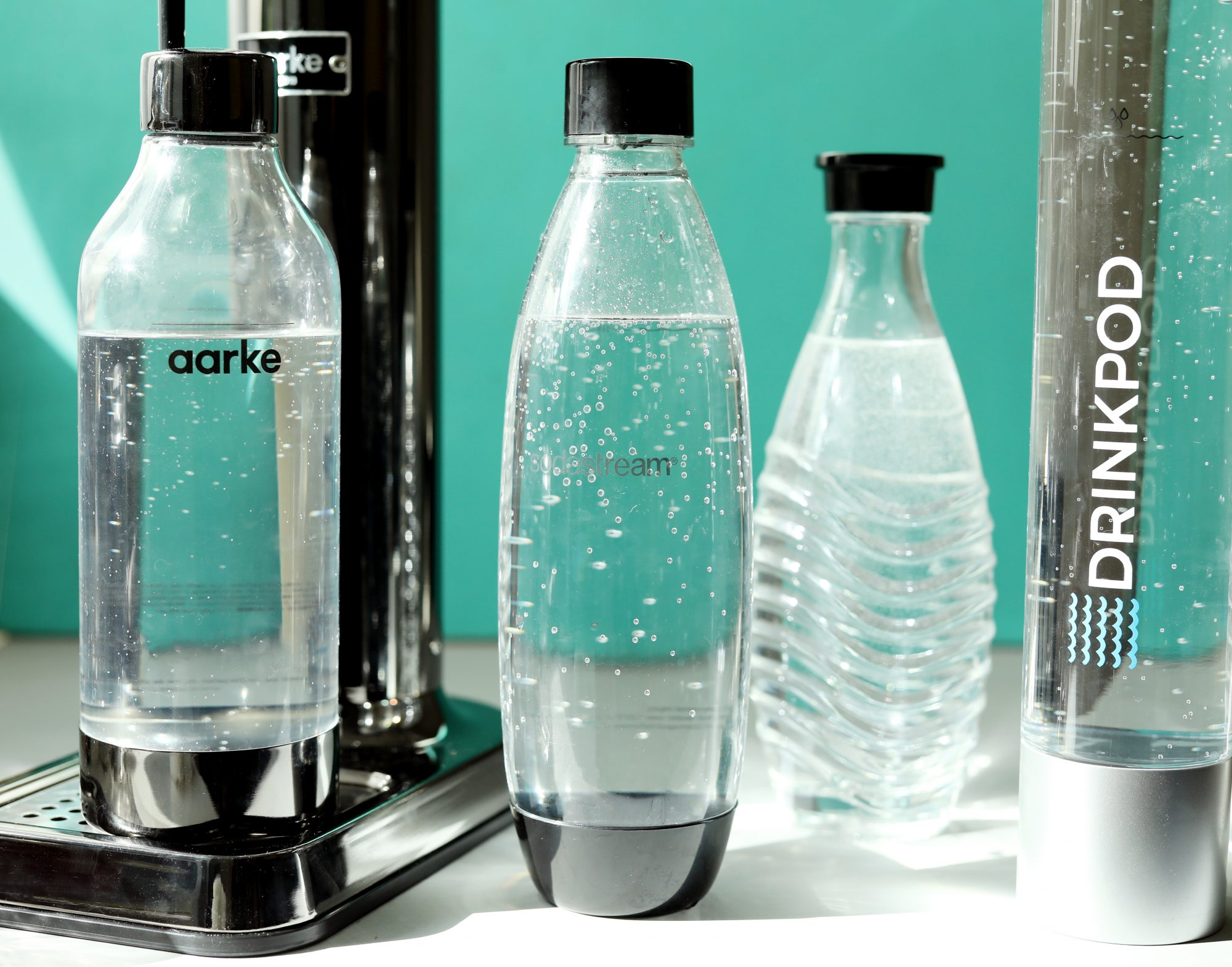 Sparkling water inside plastic soda maker containers with teal background