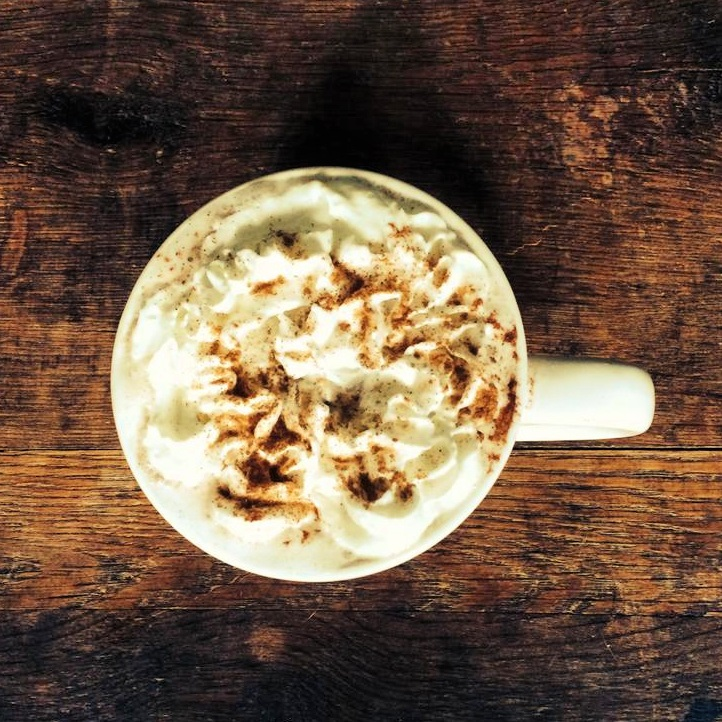 pumpkin spiced latte in a white mug topped with foam and cinnamon